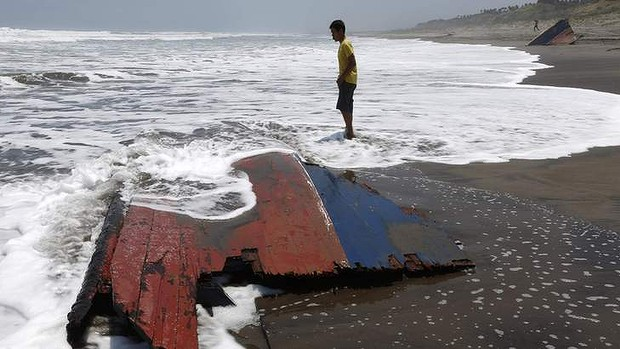 A youth standing near a piece of wreckage of a boat which sank off the Indonesian coast, at Agrabinta beach on the outskirts of Sukabumi, Indonesia's West Java province (Reuters Photo/Beawiharta) via Straits Times